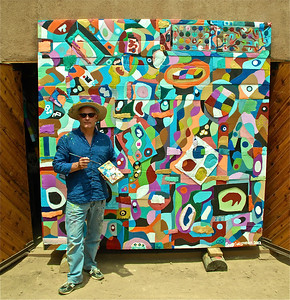 """SCOTT CHRISTOPHER IN FRONT OF HIS 8'X8' PAINTING TITLED """"CHROMOSOME #8"""" JULY, 2012. THIS PAINTING IS PART OF A TWENTY FOUR PAINTING SERIES THAT WILL MEASURE APPROXIMATELY 16'X40' WHEN COMPLETED. THE PURPOSE OF THIS WORK IS TO EXPLORE THE BEFORE, DURING, AND AFTER OF OUR EXISTENCE, ON MANY LEVELS - NOT JUST THE GENETIC CODING. I BUILD THE FRAMES AND COVER THEM WITH VARIOUS TYPES OF CARDBOARD. I PAINT THEM WITH A SPECIAL BONDING MIXTURE, AND THEN CARVE THEM WITH A CHISEL, BEFORE I BEGIN PAINTING. I HAVE ENJOYED CREATING THIS SERIES VERY MUCH. I BEGAN THIS CREATIVE PROCESS IN NOVEMBER 2011. WHEN COMPLETED, MY MURAL, WILL BE APPROXIMATELY 16'X40'."""